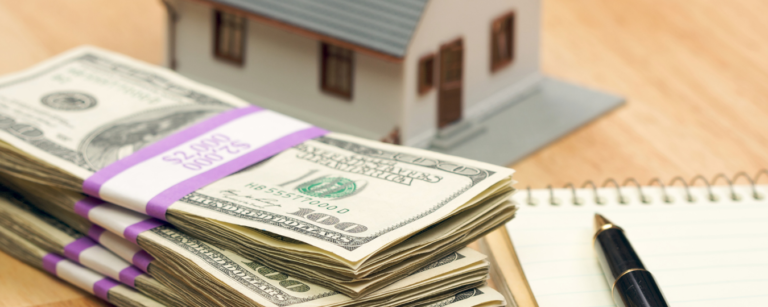 Stacks of money next to a house and a pen on top of a notebook